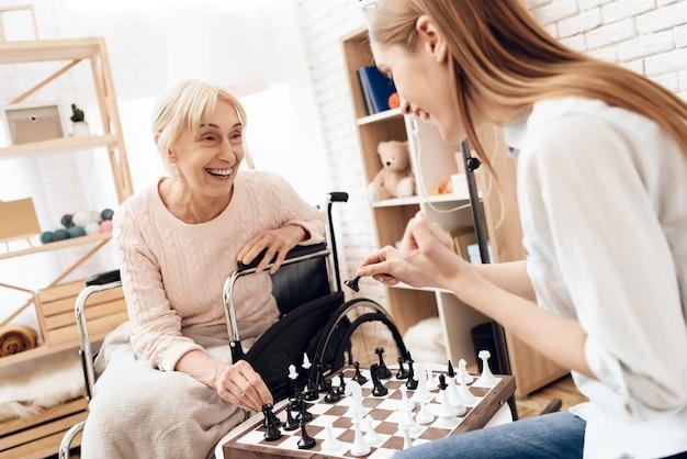 Chica joven con ajedrez de la mujer mayor en el hospital Foto Premium