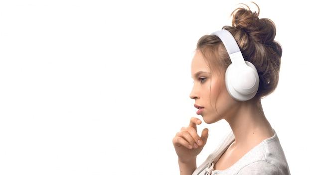 Chica joven atractiva con auriculares sobre pared blanca Foto Premium