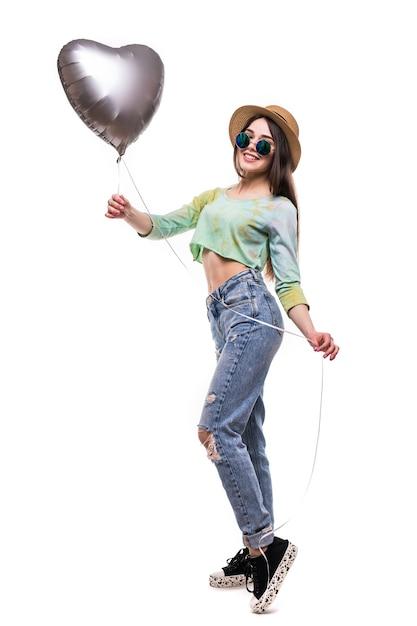 Chica joven atractiva que sostiene el globo de helio del día de san valentín aislado en blanco Foto gratis