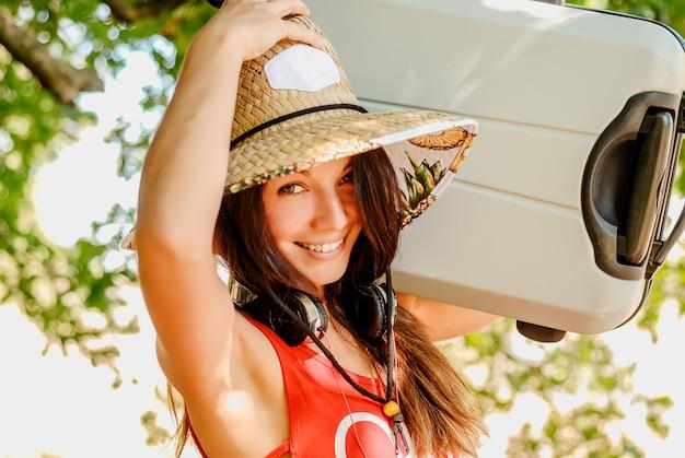 Chica joven divertida en un sombrero de paja que sostiene una maleta grande Foto Premium