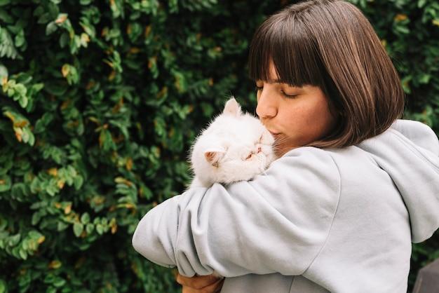 Chica joven feliz posando con su gato Foto gratis