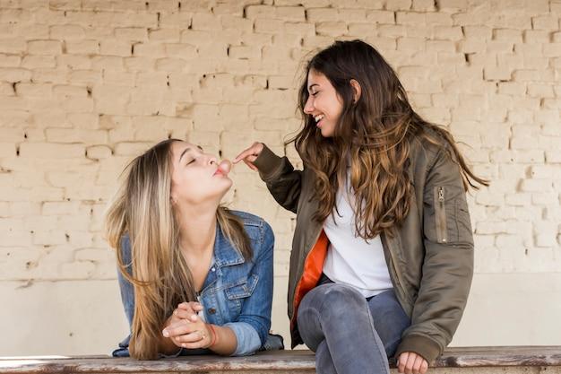Chica joven feliz que toca una burbuja soplada por su amigo con el chicle Foto gratis