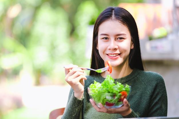 Chica joven hermosa asiática que come el vehículo de la ensalada Foto Premium