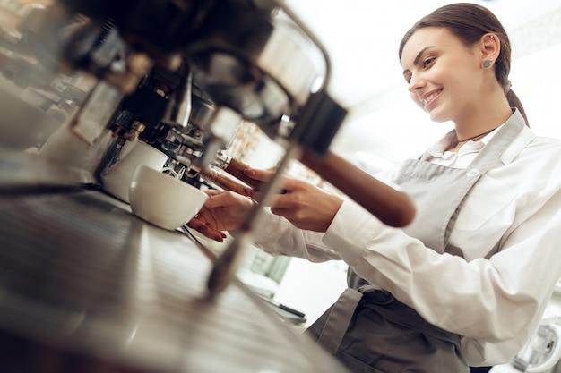 Chica joven hermosa barista que prepara el café Foto Premium