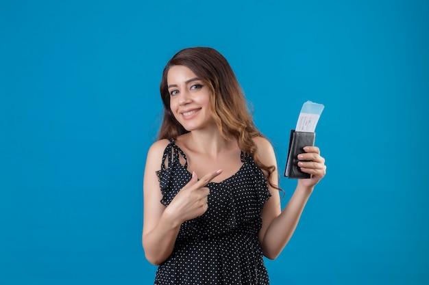 Chica joven hermosa viajera en vestido de lunares con billetes de avión mirando a cámara feliz y positivo sonriendo alegremente señalando con el dedo a los billetes de pie sobre fondo azul Foto gratis