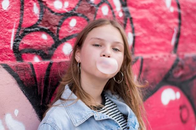 Chica joven linda que sopla el chicle contra la pared de la pintada Foto gratis