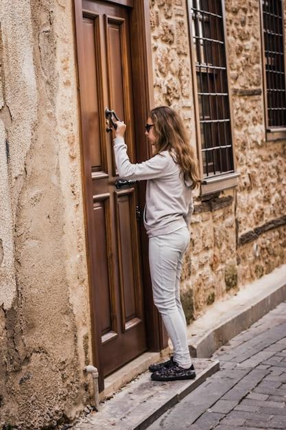 Chica joven está llamando a una puerta de madera vieja en la calle estrecha de la ciudad vieja en antalya Foto Premium