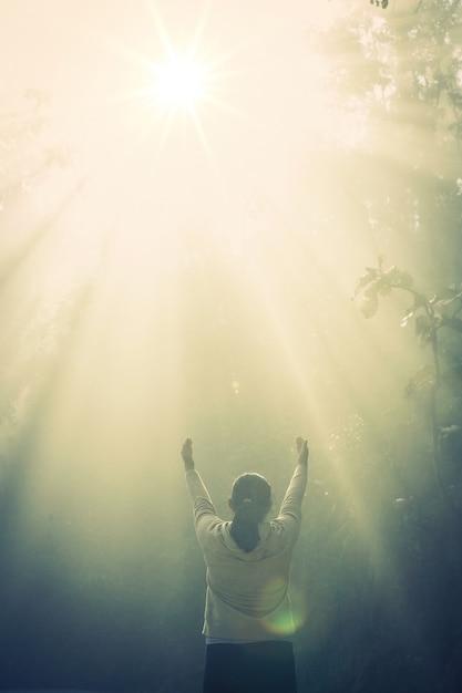 Chica joven medita en el bosque verde con luz solar Foto gratis