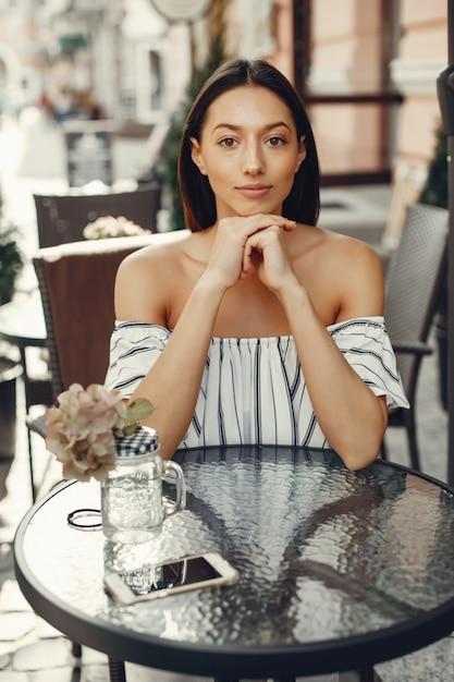 Chica joven de moda en un café de verano Foto gratis