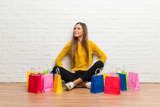 Chica joven con muchas bolsas de compras posando con los brazos en la cadera y riendo Foto Premium