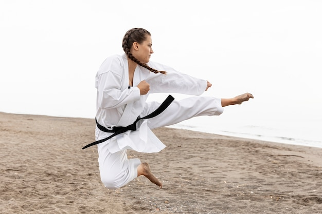 Chica joven practicando artes marciales al aire libre Foto gratis