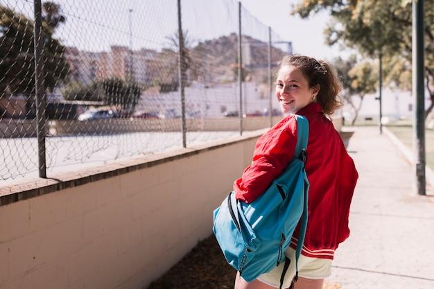 Chica joven que camina cerca de sportsground Foto gratis