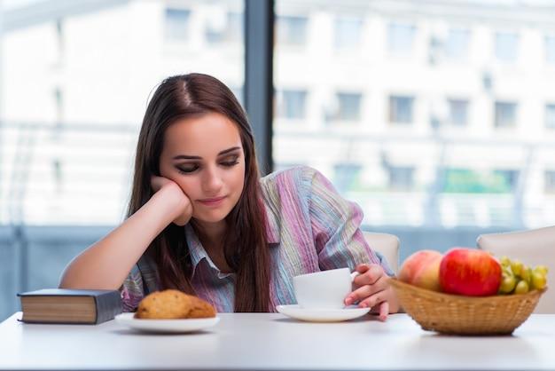 Chica joven que desayuna en la mañana Foto Premium