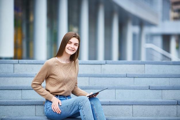 Chica joven que se sienta en los pasos y que mira en la tableta. Foto Premium