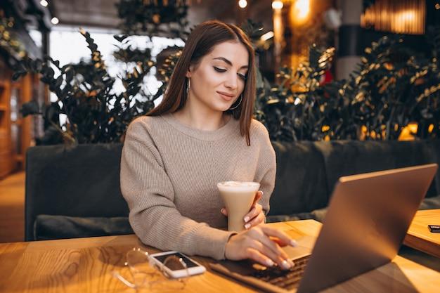 Chica joven que trabaja en una computadora en un café Foto gratis