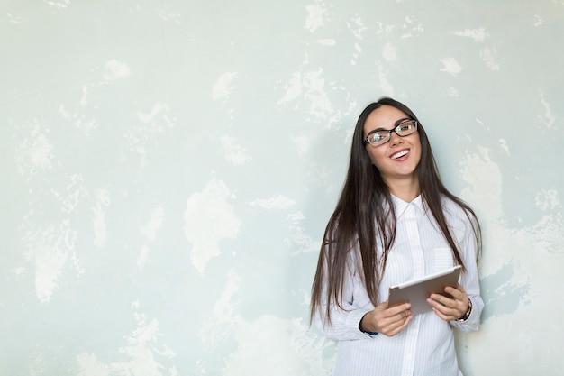 Chica joven riendo con tableta Foto gratis