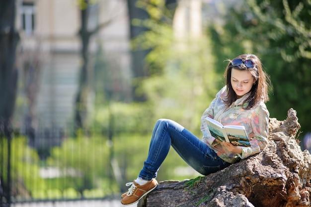 f44906522 Chica joven sentada en el parque y leyendo un libro | Descargar ...
