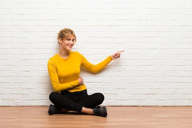 Chica joven sentada en el suelo apuntando con el dedo hacia un lado en posición lateral Foto Premium