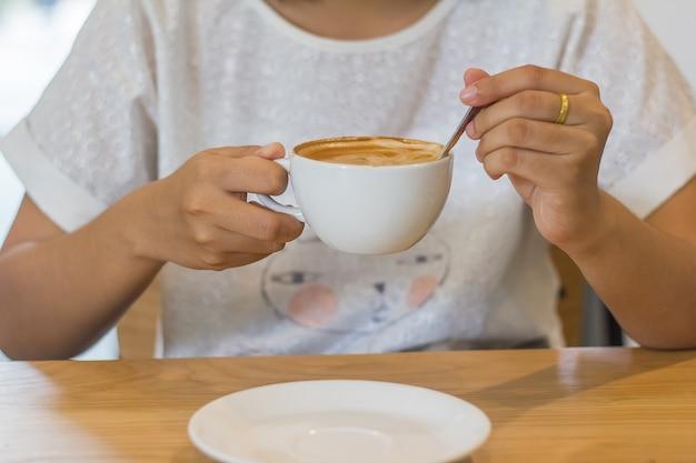 La chica joven está sentando y tomando café del latte en la cafetería. Foto Premium