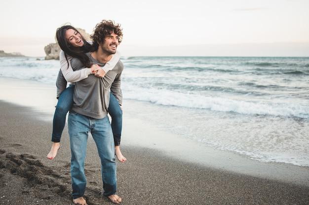 Chica jóven subida a la espalda de un hombre en la playa Foto gratis