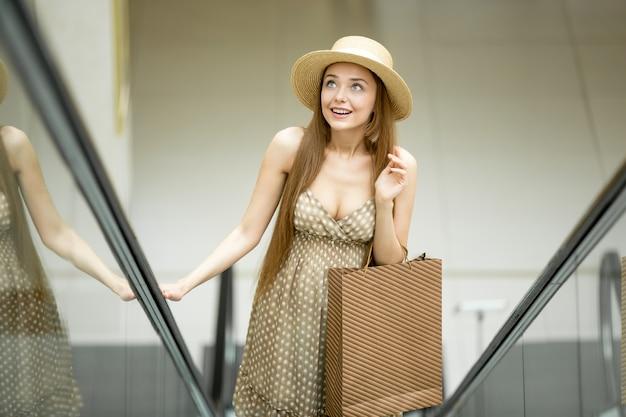 Chica joven subiendo por unas escaleras mecánicas Foto Premium
