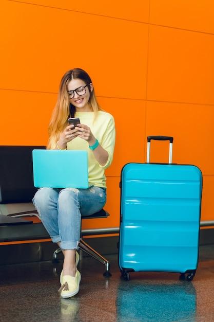 Chica joven en suÃ?Æ?Ã?©ter amarillo y jeans estÃ?Æ?Ã?Â¡ sentada en una silla sobre fondo naranja. ella tiene una computadora portÃ?Æ?Ã?Â¡til azul en las rodillas y una maleta azul cerca. ella estÃ?Æ?Ã?Â¡ escribiendo en el telÃ?Æ?Ã?©fono. Foto gratis