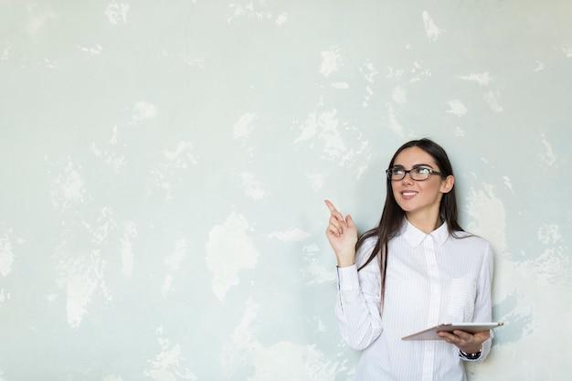 Chica joven con tableta apuntando hacia arriba Foto gratis