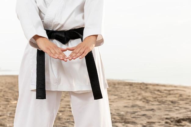 Chica joven en traje de karate al aire libre Foto gratis