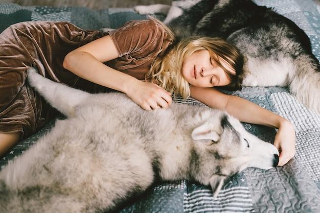 Chica joven en vestido marrón acostado en cama en casa y durmiendo con cachorro husky. el retrato interior de la forma de vida de la mujer hermosa abraza el perro fornido en el sofá. amante de mascotas. alegre mujer descansando con adorables perros. Foto Premium