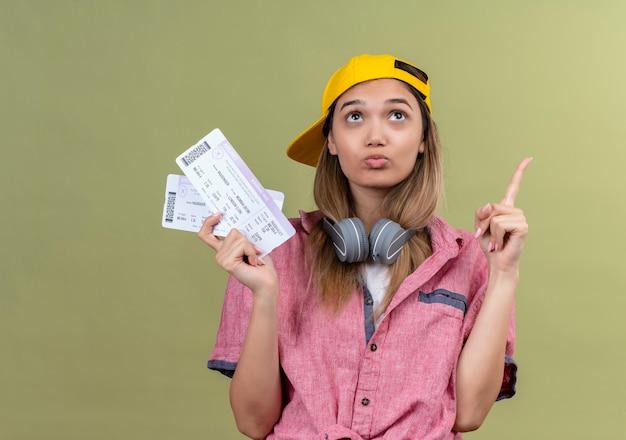 Chica joven viajero con camisa rosa en la gorra con auriculares alrededor del cuello sosteniendo boletos de avión mirando hacia arriba desconcertado dedo que apunta hacia arriba Foto gratis