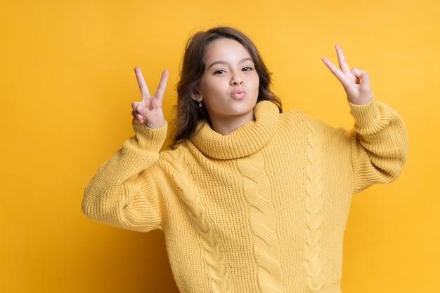 Chica juguetona mostrando retrato de signo de la paz Foto gratis