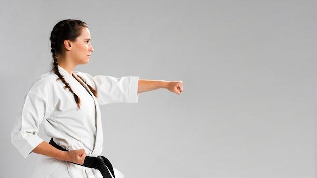 Chica de karate de artes marciales con cinturón negro y copia espacio de fondo Foto Premium