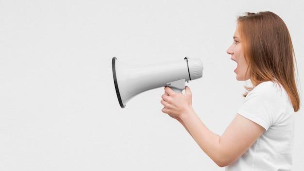 Chica de lado gritando en megáfono Foto gratis