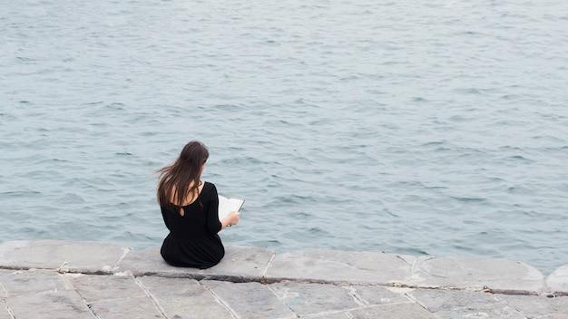 Chica leyendo un libro en la calle Foto gratis