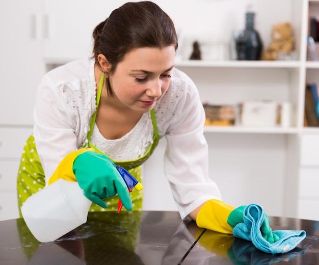 Chica limpia mesa en casa Foto Gratis