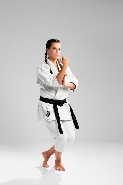 Chica luchadora en posición de combate vistiendo el uniforme blanco sobre fondo gris Foto gratis