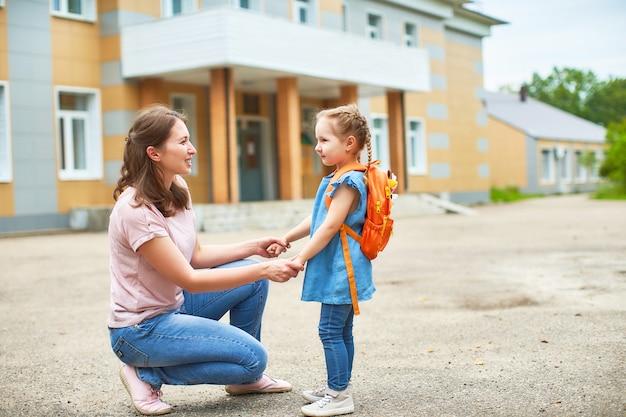 Chica con maletines cerca de la escuela. Foto Premium