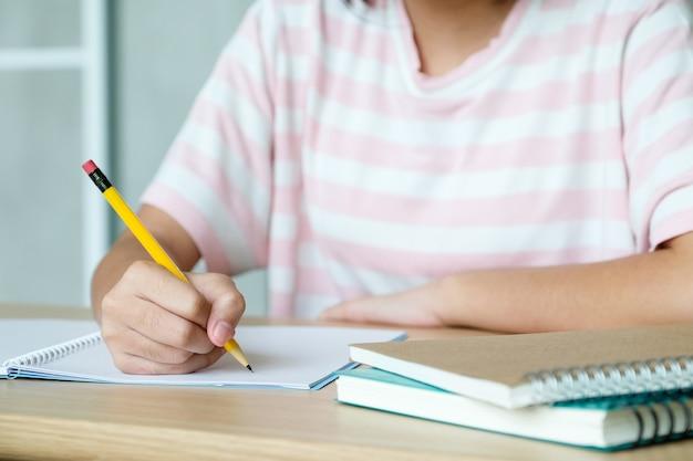 Chica mano escribir cuaderno de papel sobre la mesa, concepto de educación Foto Premium