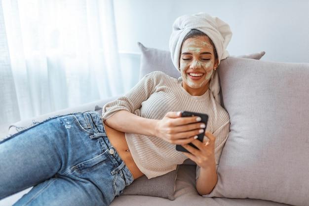 Chica con máscara de belleza relajante en casa, mensajes de texto por teléfono celular Foto Premium
