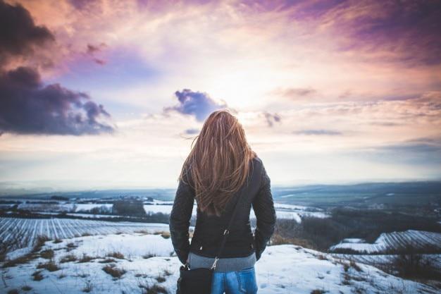 Chica mirando el paisaje de invierno Foto Gratis