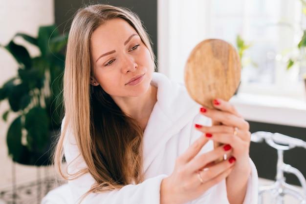 Chica mirándose a un espejo Foto gratis