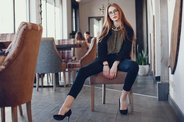 Chica de moda en un café Foto gratis