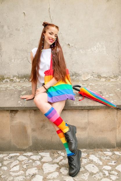 Chica de moda en calcetines coloridos con botas masculinas. elegante lesbiana con lgbt rainbow en su cara posando al aire libre Foto Premium