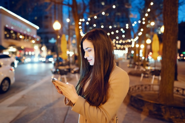 Chica de moda caminando en una ciudad de noche Foto gratis