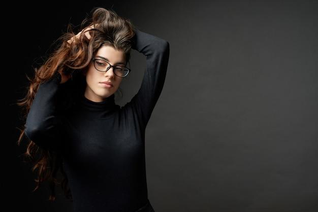Chica de moda de negocios con gafas sobre fondo gris oscuro Foto Premium