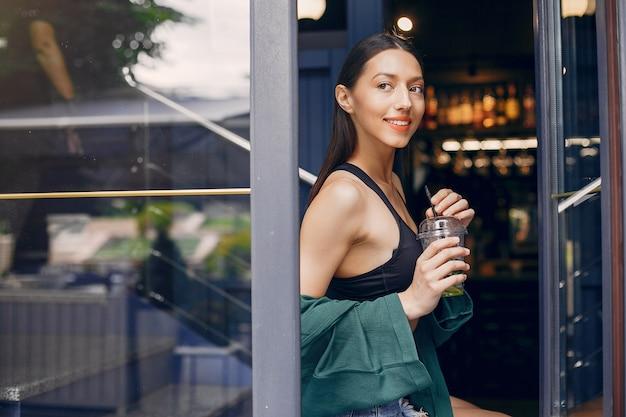 Chica de moda de pie en un café de verano Foto gratis