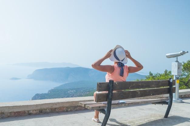 Chica de moda en sombrero blanco se sienta en un banco y disfruta de vistas al mar y las montañas. Foto Premium
