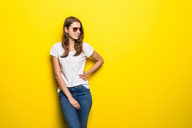 Chica de moda sonriente en camiseta blanca y pantalones de mezclilla permanecer delante de fondo de estudio amarillo Foto gratis