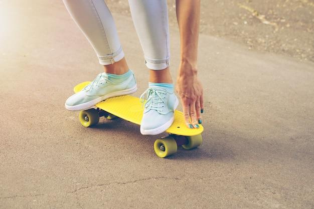 Chica monta en la carretera en un monopatín de plástico en la luz del sol Foto Premium