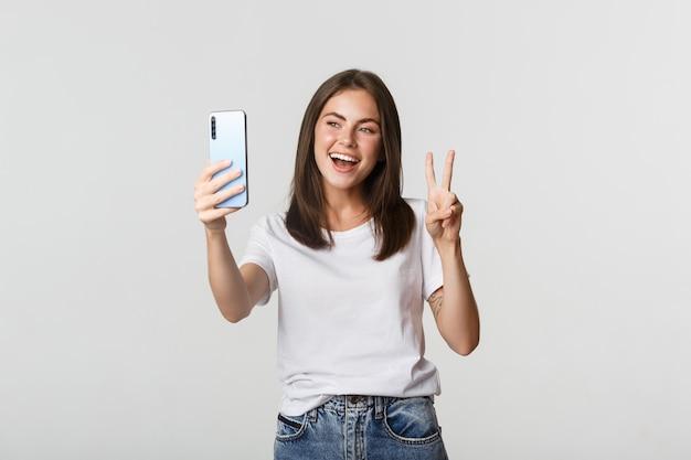 Chica morena atractiva mirando feliz y tomando selfie en smartphone Foto Premium